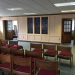 The stained glass, paneling, and chairs from the old Chapel finds a new home in the Parlor.